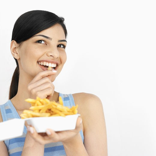 Close-up of young woman eating carton of French fries : Stock Photo
