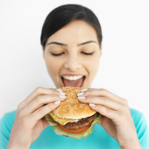 Stock Photo: 1491R-1072138 Front view portrait of young woman eating burger