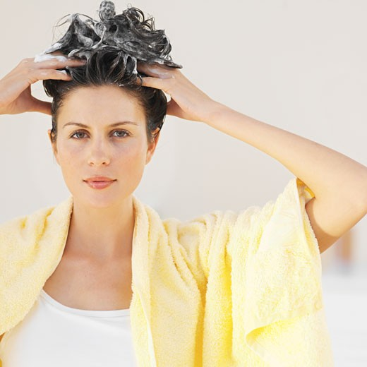 Front view portrait of a woman washing her hair : Stock Photo