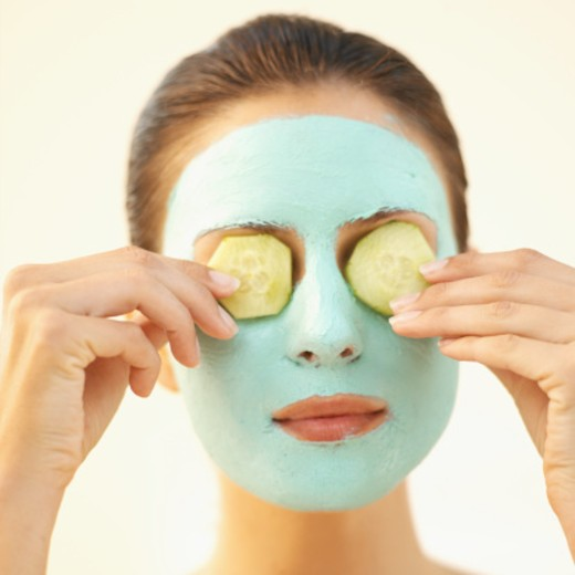 Front view head-shot of a woman wearing face mask and cucumber slices covering her eyes : Stock Photo