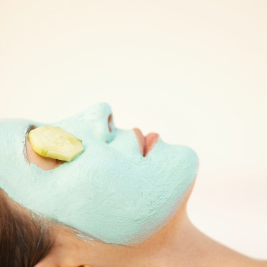 Side view close-up of a woman wearing face mask and cucumber slices covering her eyes : Stock Photo