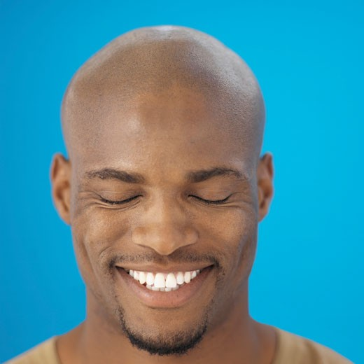 Front view portrait of young man smiling with eyes closed : Stock Photo