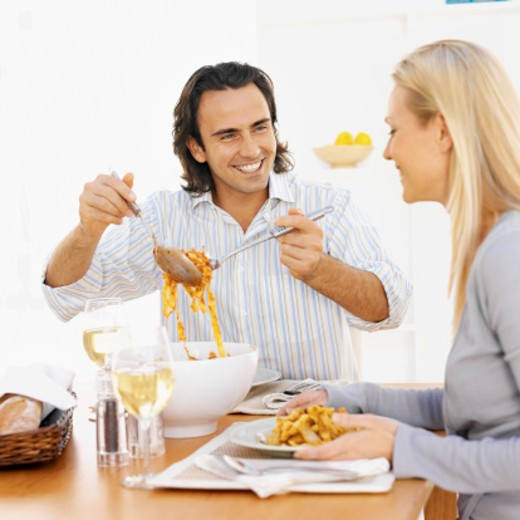 Close-up of young man serving food to young woman : Stock Photo