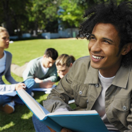 Close-up of four young people sitting on grass and studying : Stock Photo
