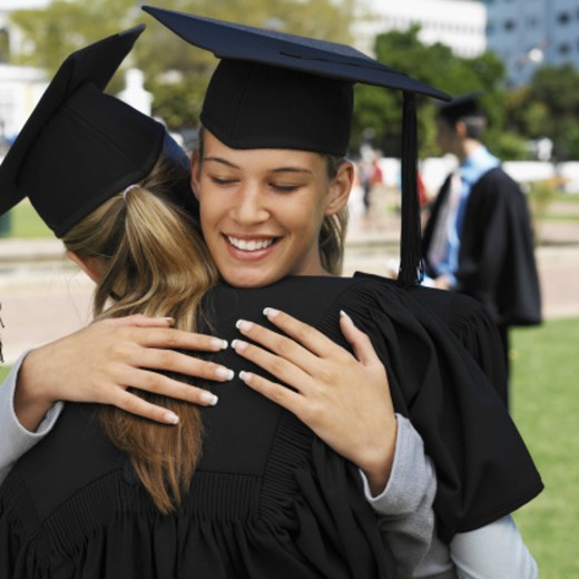 Close-up of two young women hugging wearing cap and gown with other person in background : Stock Photo