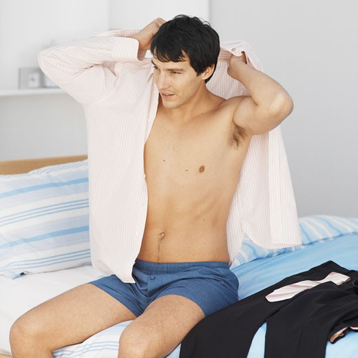 Stock Photo: 1491R-1072928 Close-up of young man putting shirt on while sitting on bed