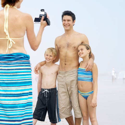 Mother filming his family at the beach : Stock Photo