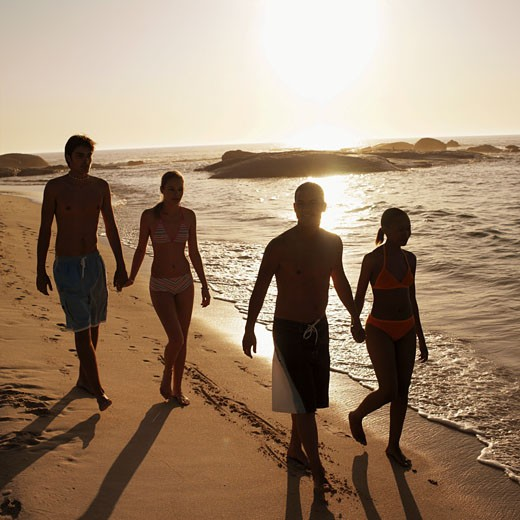 Front view of four young people walking on beach : Stock Photo