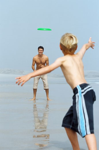 Father and son (10-11)playing with a plastic disk at the beach : Stock Photo