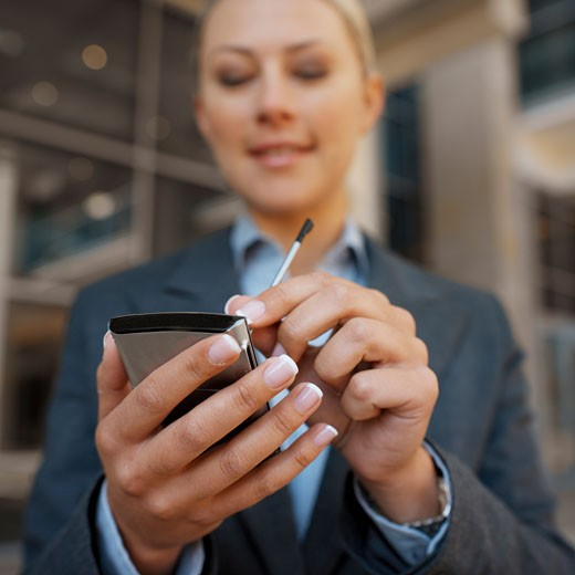 Low angle view of a businesswoman using a PDA : Stock Photo