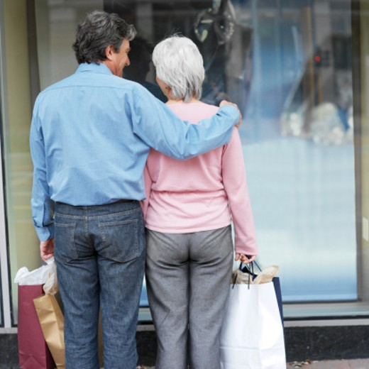 Stock Photo: 1491R-1073467 Rear view of senior couple looking at shop window and holding shopping bags