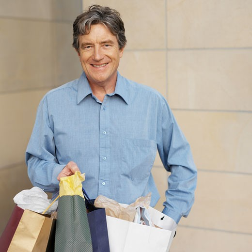 Stock Photo: 1491R-1073479 Front view portrait of senior man holding shopping bags
