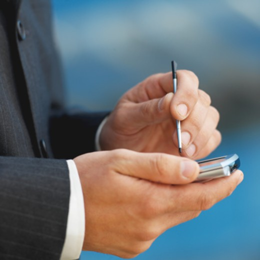 Close-up side view of a businessman's hands using a PDA : Stock Photo