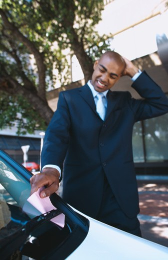 Young businessman taking a parking ticket from the windshield of his car : Stock Photo