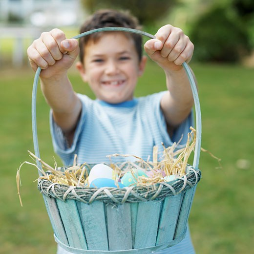 Boy (7-8) holding up a basket of Easter eggs : Stock Photo