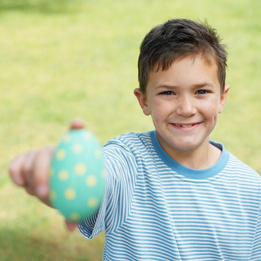 Boy (7-8) holding up an Easter egg : Stock Photo
