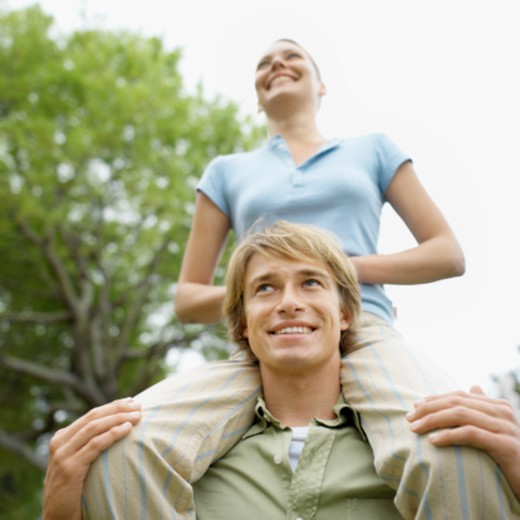Man with a woman on his shoulders : Stock Photo