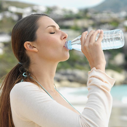 Stock Photo: 1491R-1074095 Low angle side view of a woman drinking water from a bottle