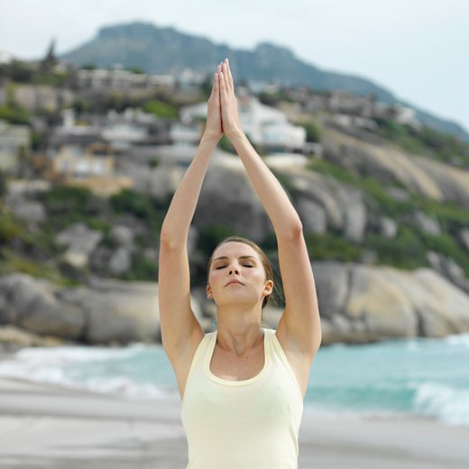 Stock Photo: 1491R-1074098 Front view of a woman doing yoga at the beach