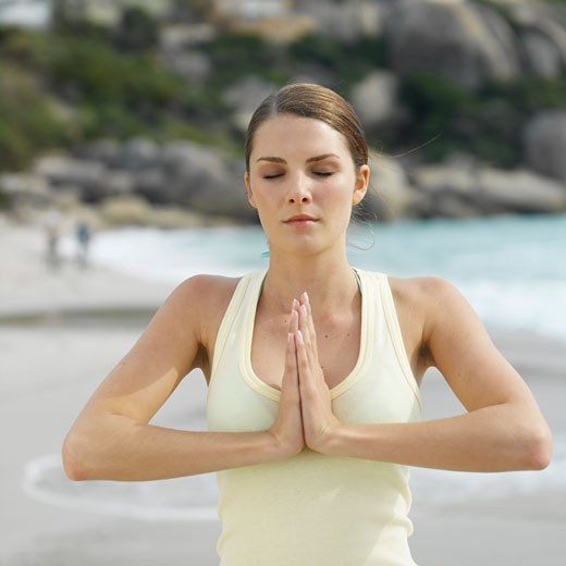 Front view of a woman doing yoga at the beach : Stock Photo
