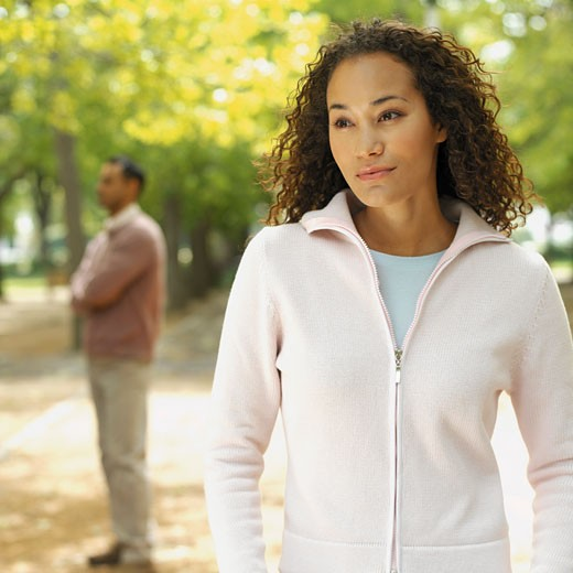 Close-up of a young woman with mid adult man in the background : Stock Photo
