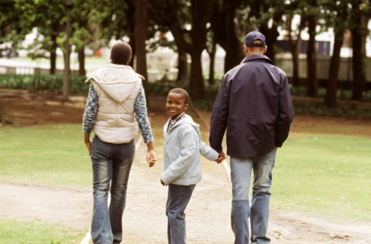 Rear view of parents and son walking in park (10-11) : Stock Photo