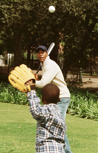 Stock Photo: 1491R-1074383 Father and son playing baseball in garden (8-9)