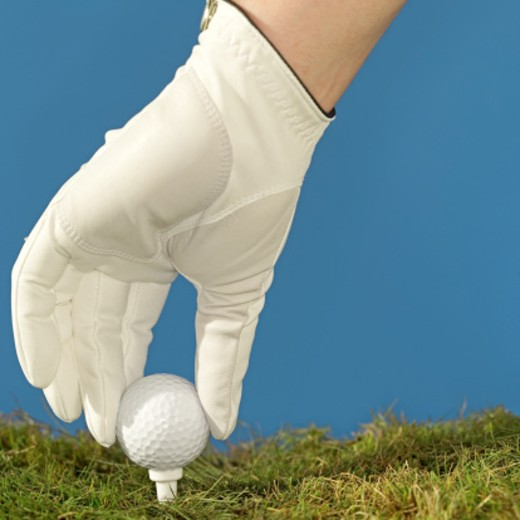 Stock Photo: 1491R-1074636 Close-up of a person's hand placing golf ball on tee