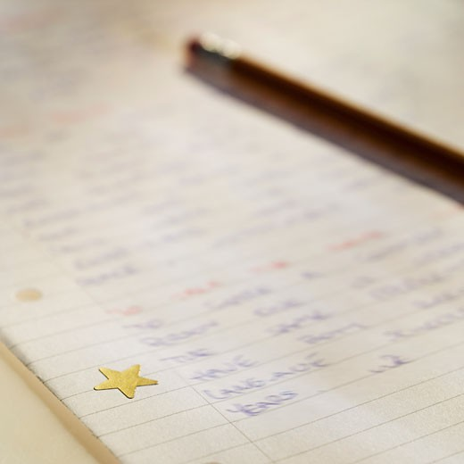 Close-up of written homework with gold star and pencil : Stock Photo