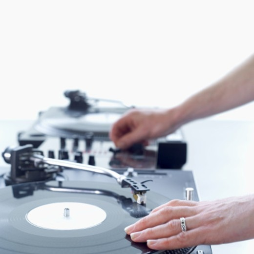 DJ hands mixing on decks : Stock Photo