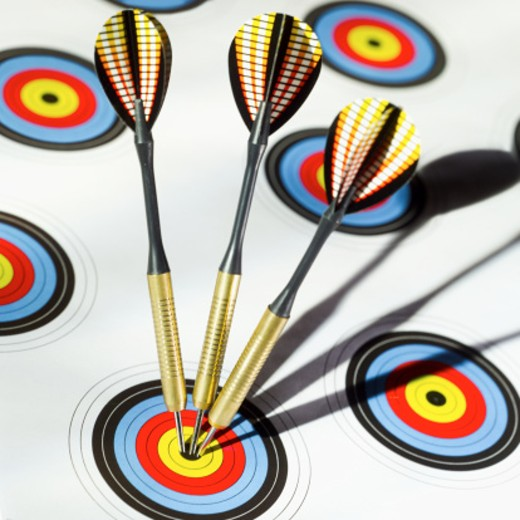 Close-up of three darts in bulls eye of target : Stock Photo