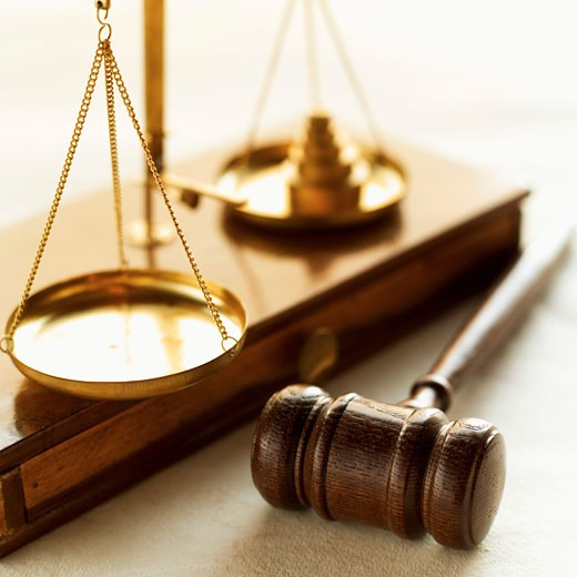 Stock Photo: 1491R-1075630 Close-up of weights balancing scales of justice with gavel beside it