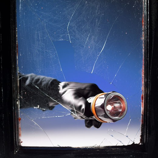Stock Photo: 1491R-1075741 Close-up of man's hand breaking glass with torch