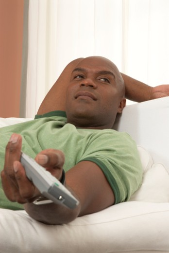 Man using remote control on couch : Stock Photo