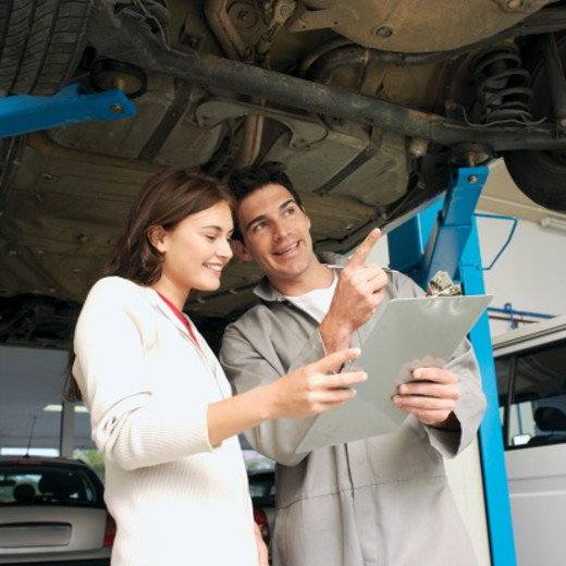 Car mechanic holding clipboard and talking to female customer in garage : Stock Photo