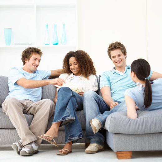 Four friends sitting on sofa talking : Stock Photo