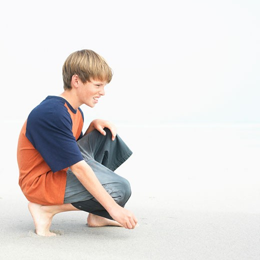 Stock Photo: 1491R-1078717 Boy (12-13) crouching on beach, profile