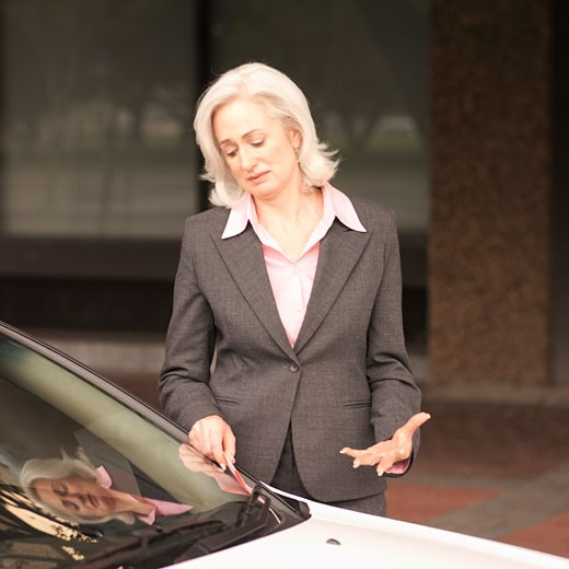Mature businesswoman taking out parking ticket put under wiper : Stock Photo