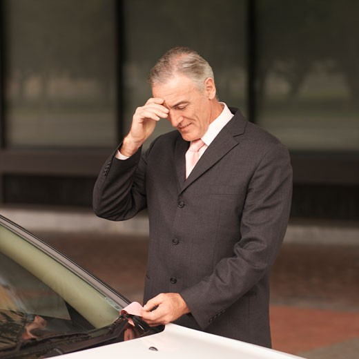 Stock Photo: 1491R-1078788 Mature businessman taking out parking ticket put under wiper