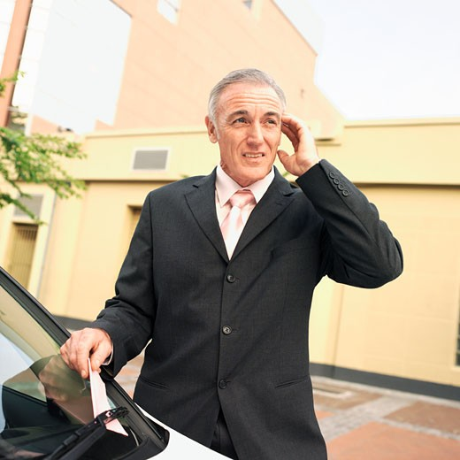 Mature businessman taking out parking ticket put under wiper : Stock Photo