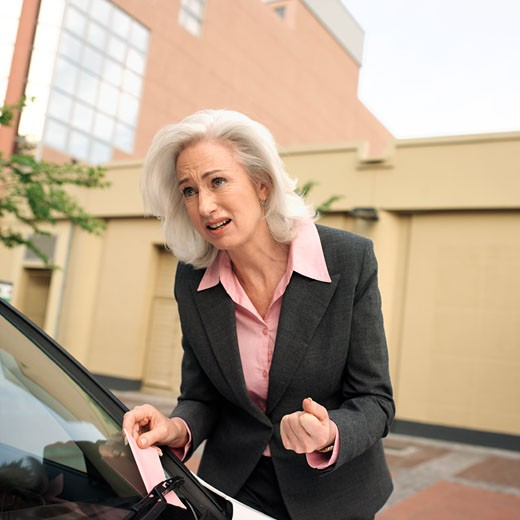 Stock Photo: 1491R-1078792 Mature businesswoman taking out parking ticket put under wiper