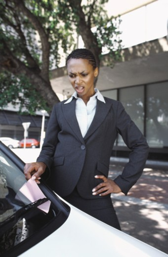 Business woman removing parking ticket from car : Stock Photo