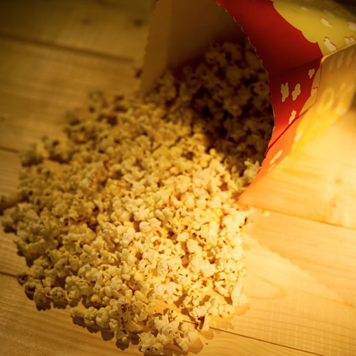 Popcorn spilling from container onto wooden table : Stock Photo