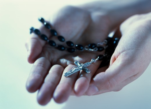 Person holding rosary, close-up of hands : Stock Photo