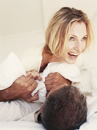 Stock Photo: 1491R-1079097 Couple having pillow fight on bed
