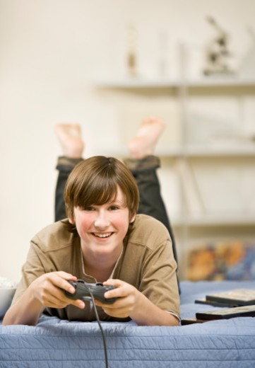 Stock Photo: 1491R-1079515 Teenage boy (13-14) playing video games on bed, portrait