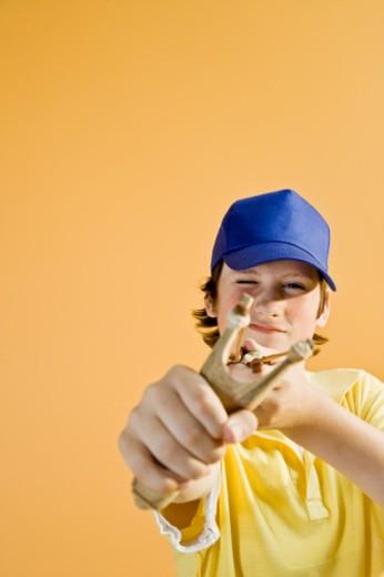 Stock Photo: 1491R-1079518 Teenage boy (13-14) aiming slingshot, portrait
