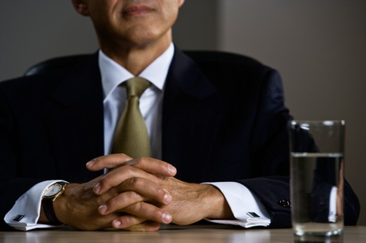 Stock Photo: 1491R-1079562 Mature businessman with hands clasped on desk, mid section