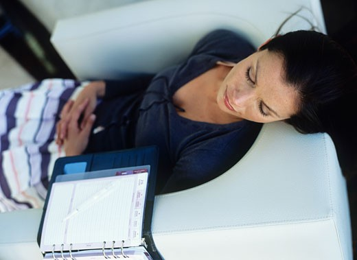 Stock Photo: 1491R-1079637 Mid adult woman lying down on sofa,open diary beside,high angle view