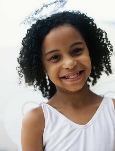 Girl (10-11) with halo over head and angel wings,smiling,portrait,close-up : Stock Photo
